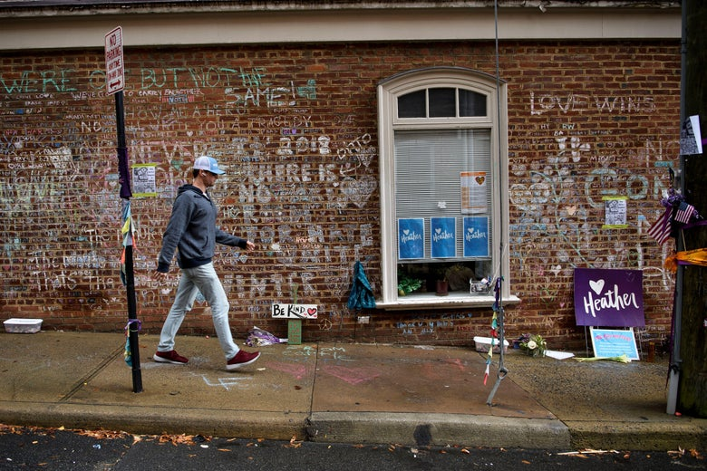 A man walks past a memorial to Heather Heyer and the other victims of a deadly hit and run by neo-Nazi James Fields.