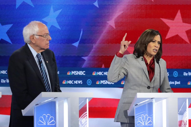 Sanders and Harris stand at lecterns in front of an American flag background.