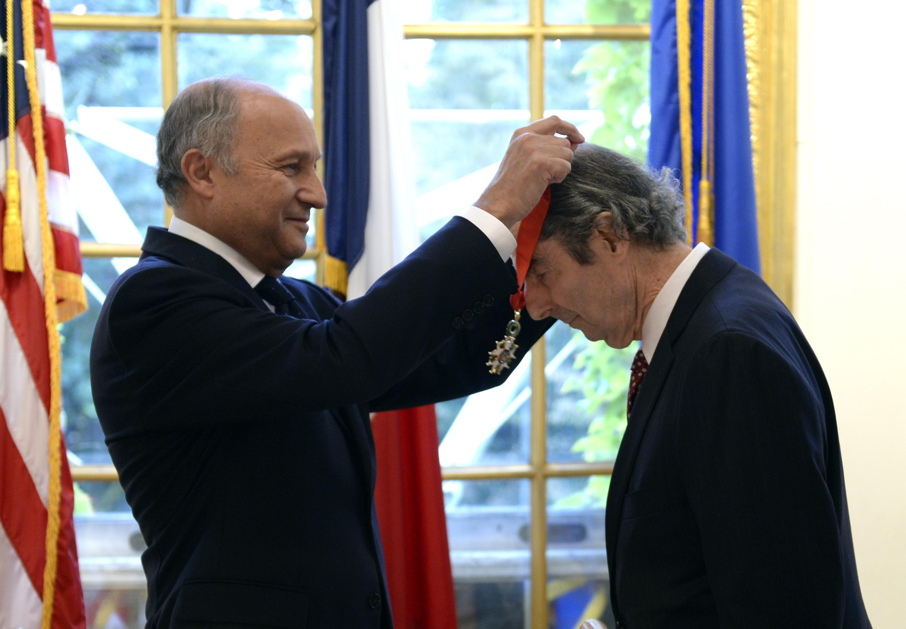 French Foreign Minister Laurent Fabius puts a medal around the neck of Philip Roth.