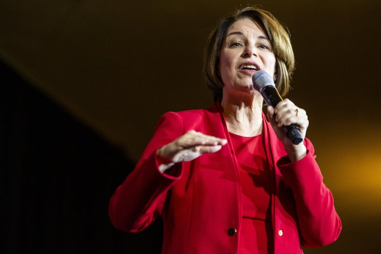 Amy Klobuchar gestures with one hand while holding a microphone in the other.