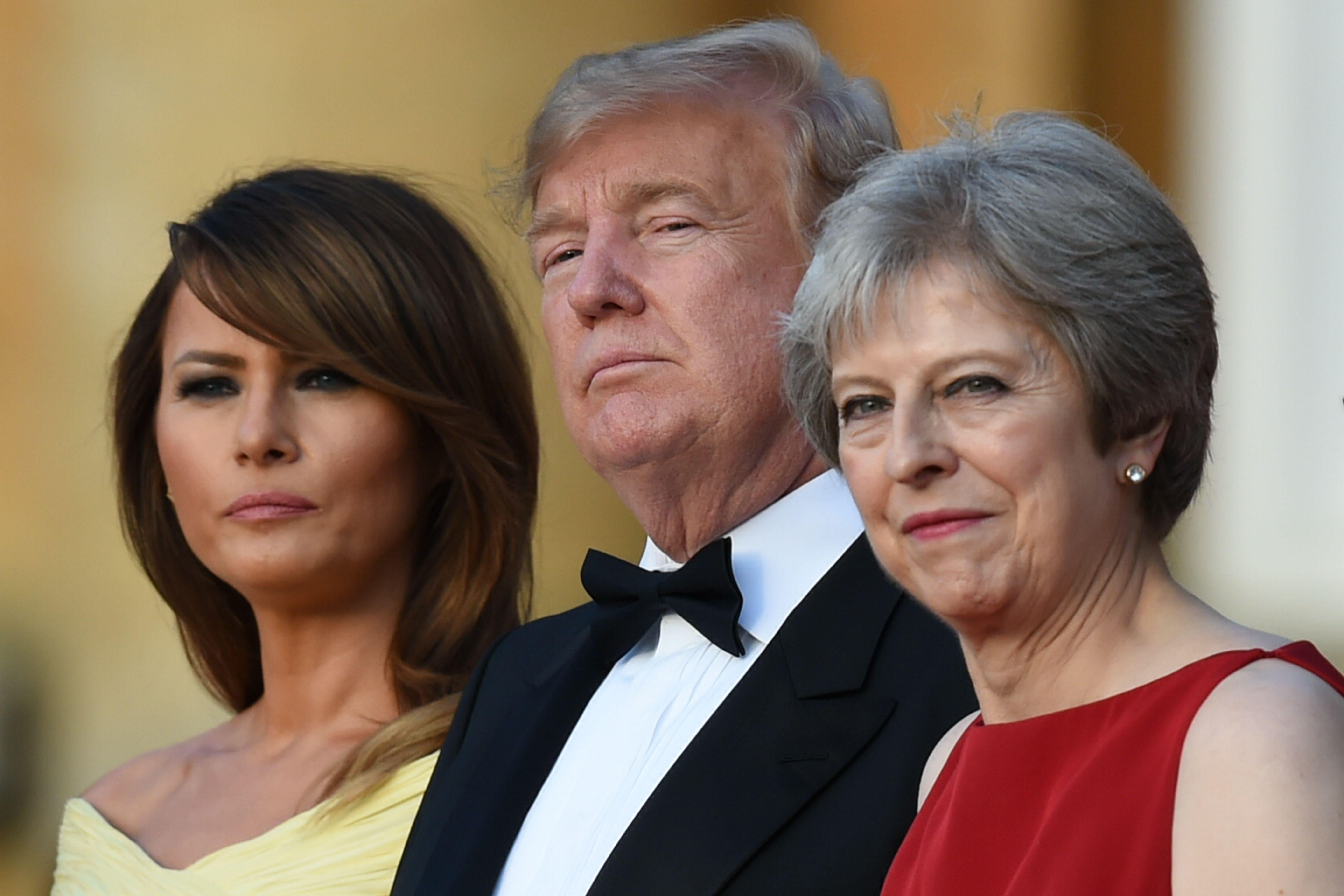 First Lady Melania Trump, President Donald Trump and Britain's Prime Minister Theresa May stand on steps during a ceremonial welcome at Blenheim Palace on July 12, 2018.