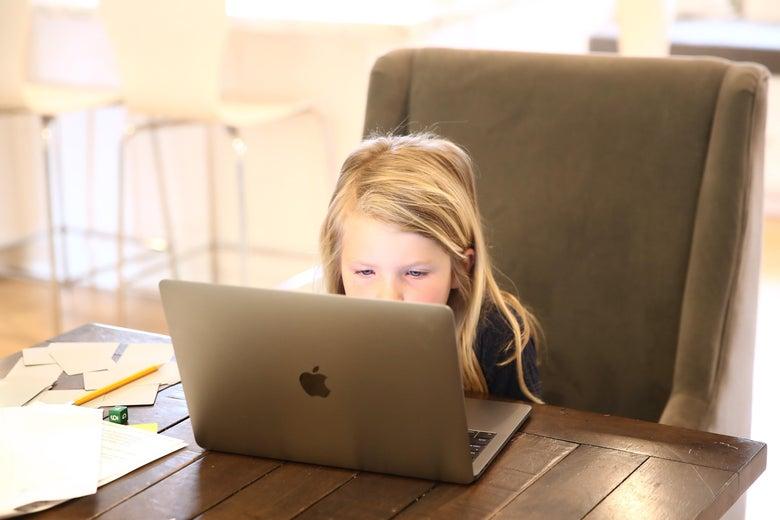 A kindergartener sits at a laptop for remote schooling.