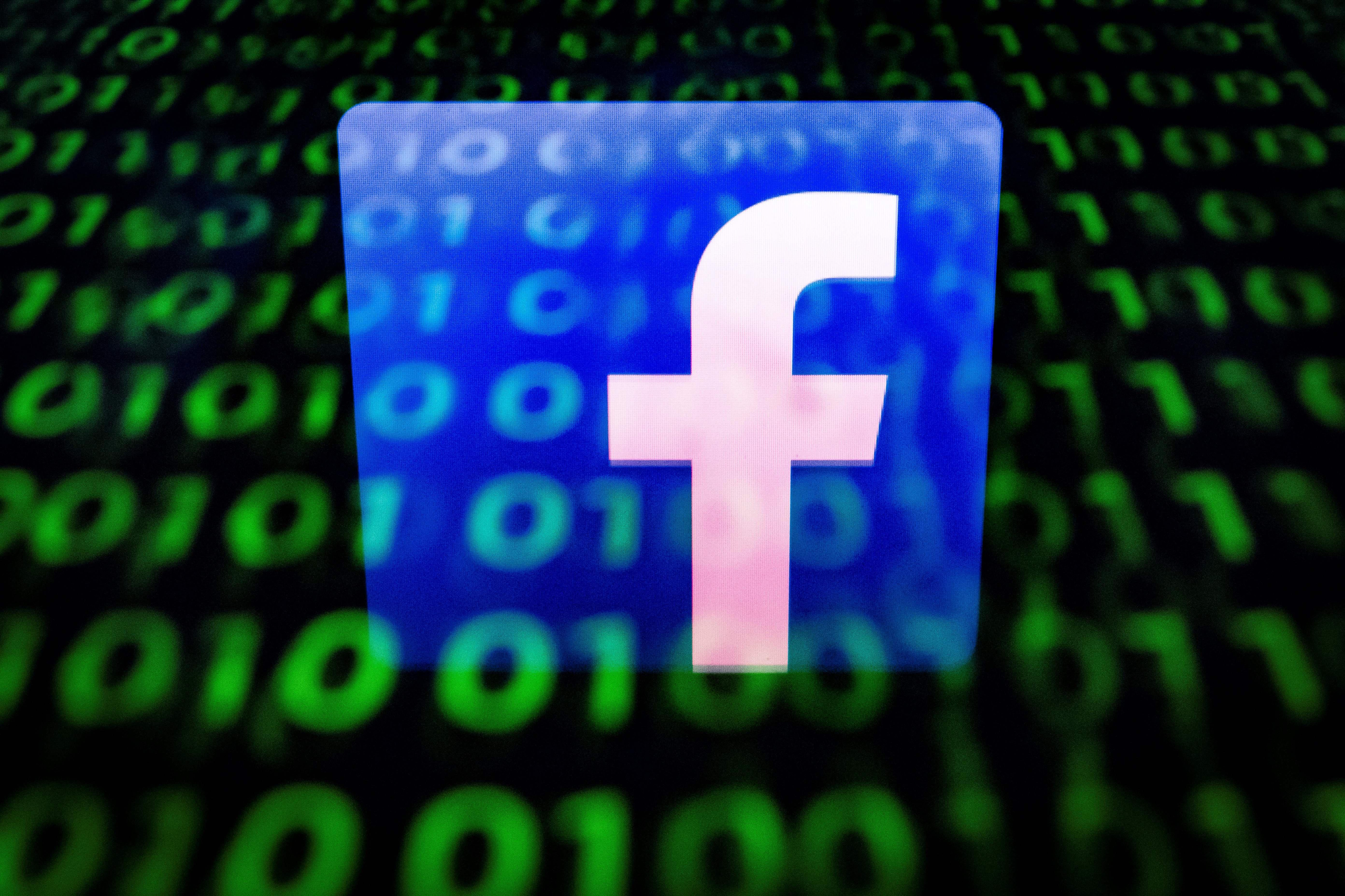 The Facebook logo faded over a screen of binary code