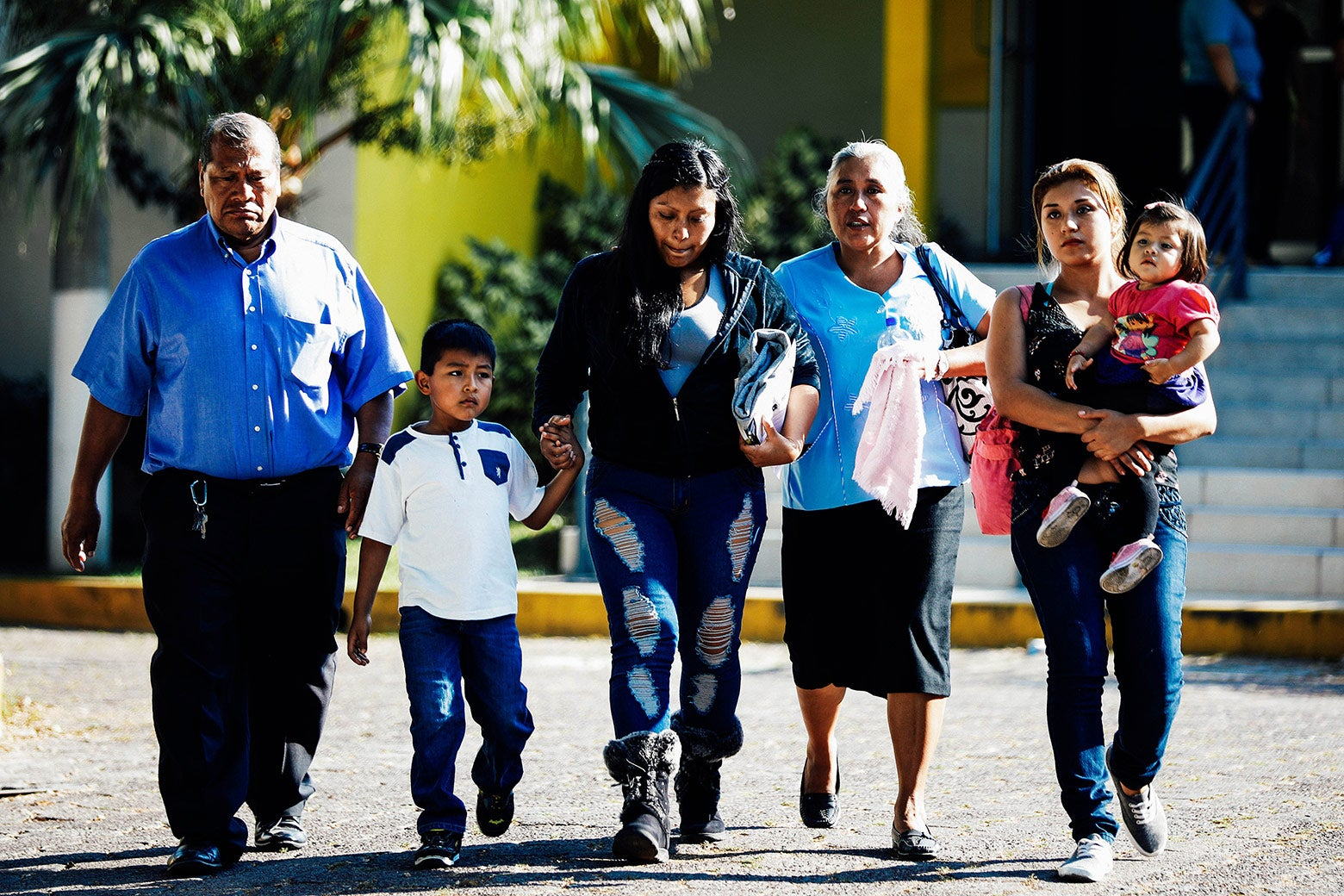 A deportee walks out with her family at an immigration facility in San Salvador, El Salvador, on Jan. 11.