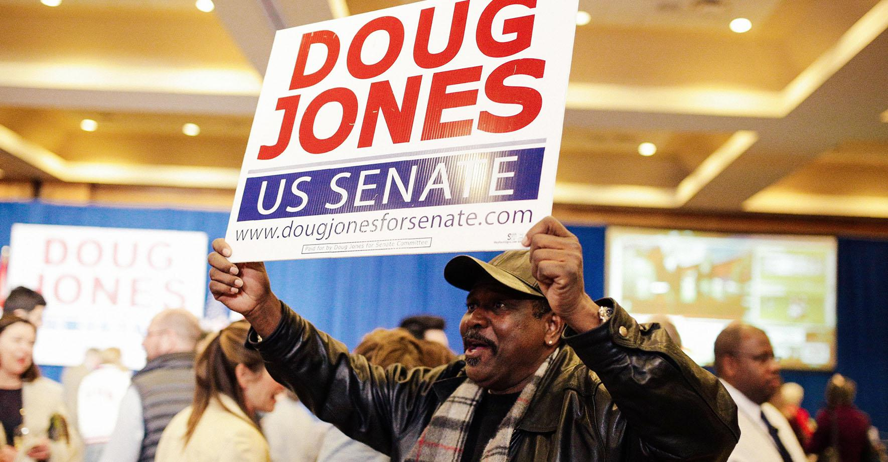A supporter holds a sign during Democratic U.S. Senate candidate Doug Jones' election night party in Birmingham, Alabama, U.S. December 12, 2017.