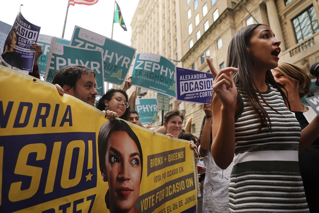 Ocasio-Cortez speaks outdoors in front of supporters holding signs and a banner.