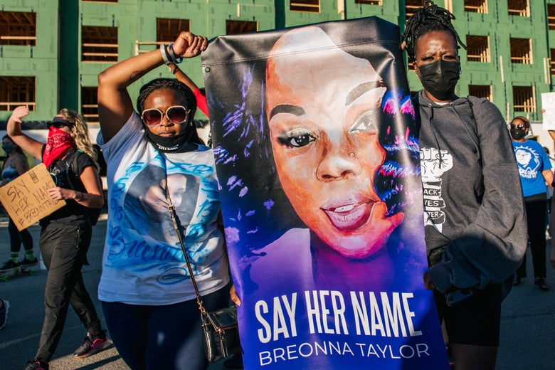"Two women at the front of a march hold a sign featuring an illustration of Breonna Taylor's face and the words ""Say her name, Breonna Taylor."""
