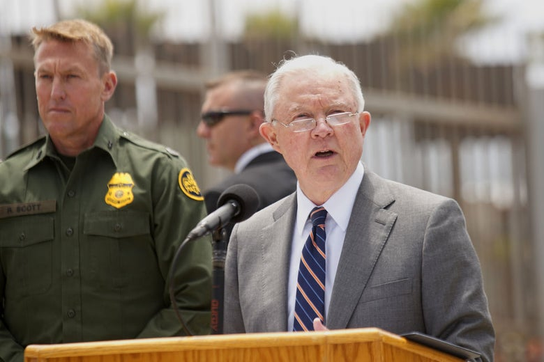 Sessions delivering a speech while standing by a border guard near what appears to be a fence.