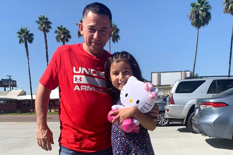 A man stands with his daughter, who is carrying a Hello Kitty toy.