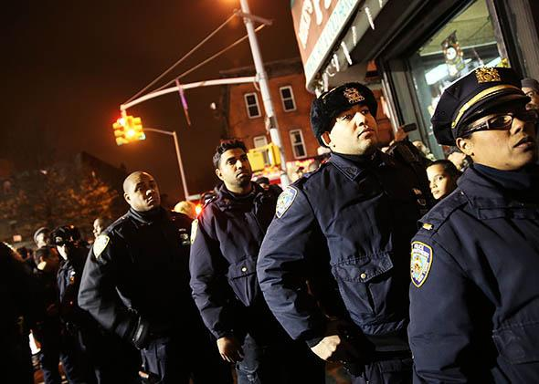 Police officers line-up to pay their respects at a memorial during a vigil for two New York City police officers at the location where they were killed.