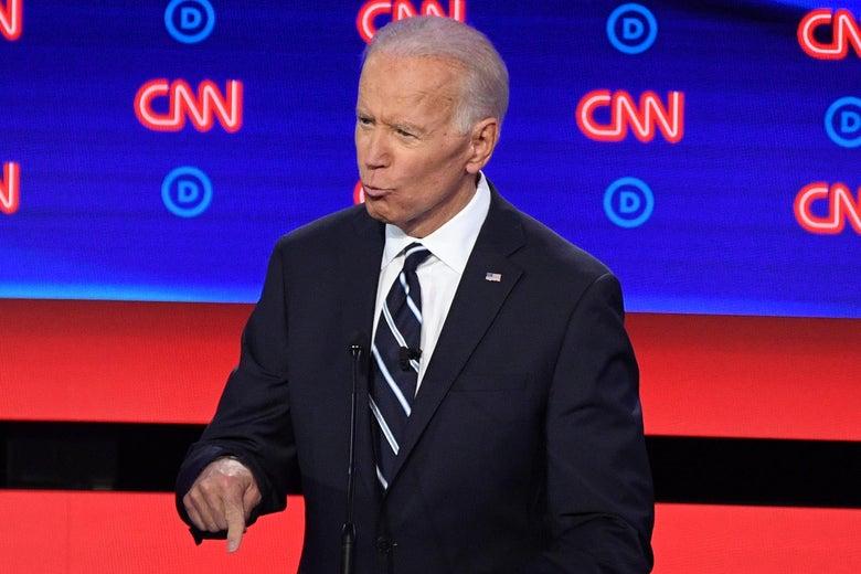 Joe Biden speaks behind a podium, pointing his index finger.
