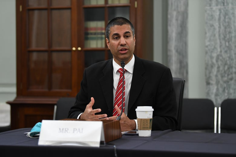 Former Chairman of Federal Communications Commission Ajit Pai sits at a table with a cup of coffee as he gestures with his hands.