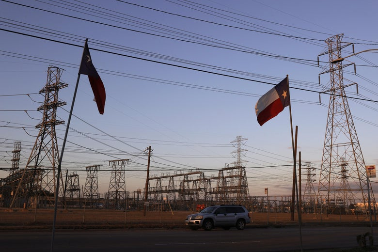 Two Texas flags and a silver SUV are seen in front of an electrical substation, with a number of towers, poles, and wires.