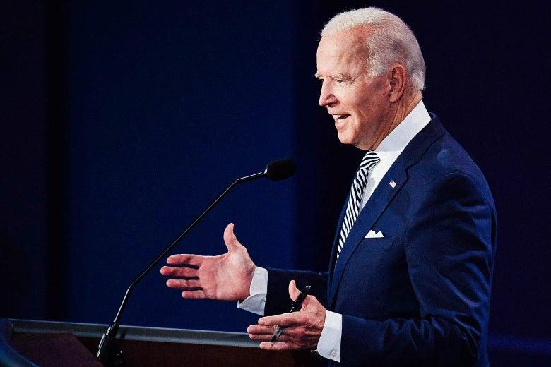 Joe Biden shrugs while standing behind a podium.