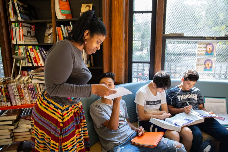A young librarian drops by as a group of teens do their homework together.