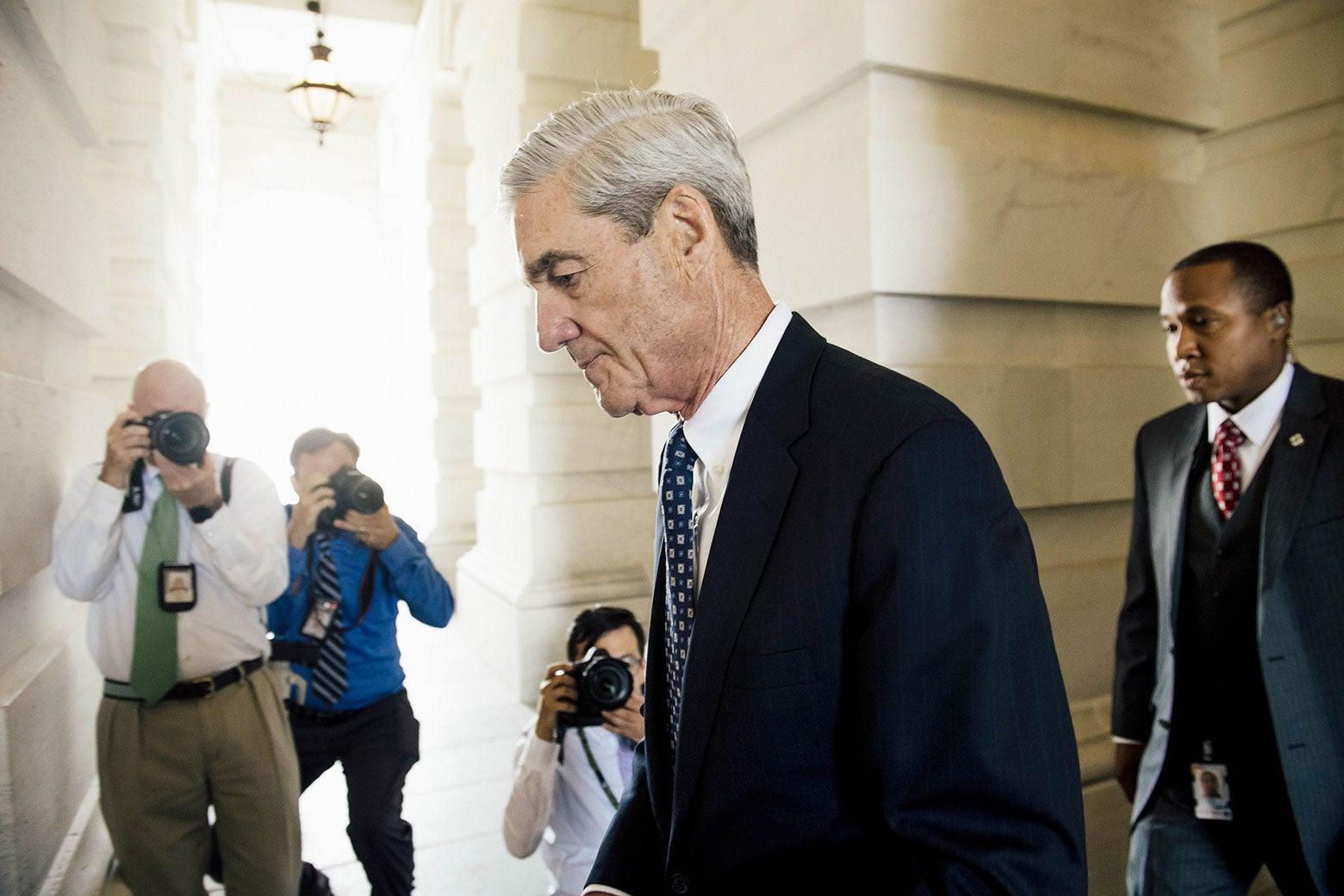 Robert Mueller walks out of a building.