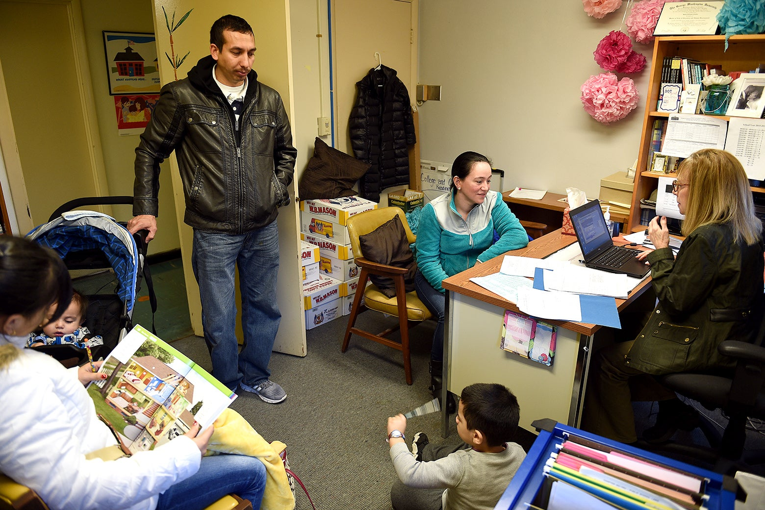 Maura Salguero, sitting, center, processes her daughter Jennifer Garcia Salguero, 12, left, at the International Student Counseling Office at the Judy Hoyer Learning Center of Cool Spring Elementary School in Adelphi, MD on Jan. 13, 2016.