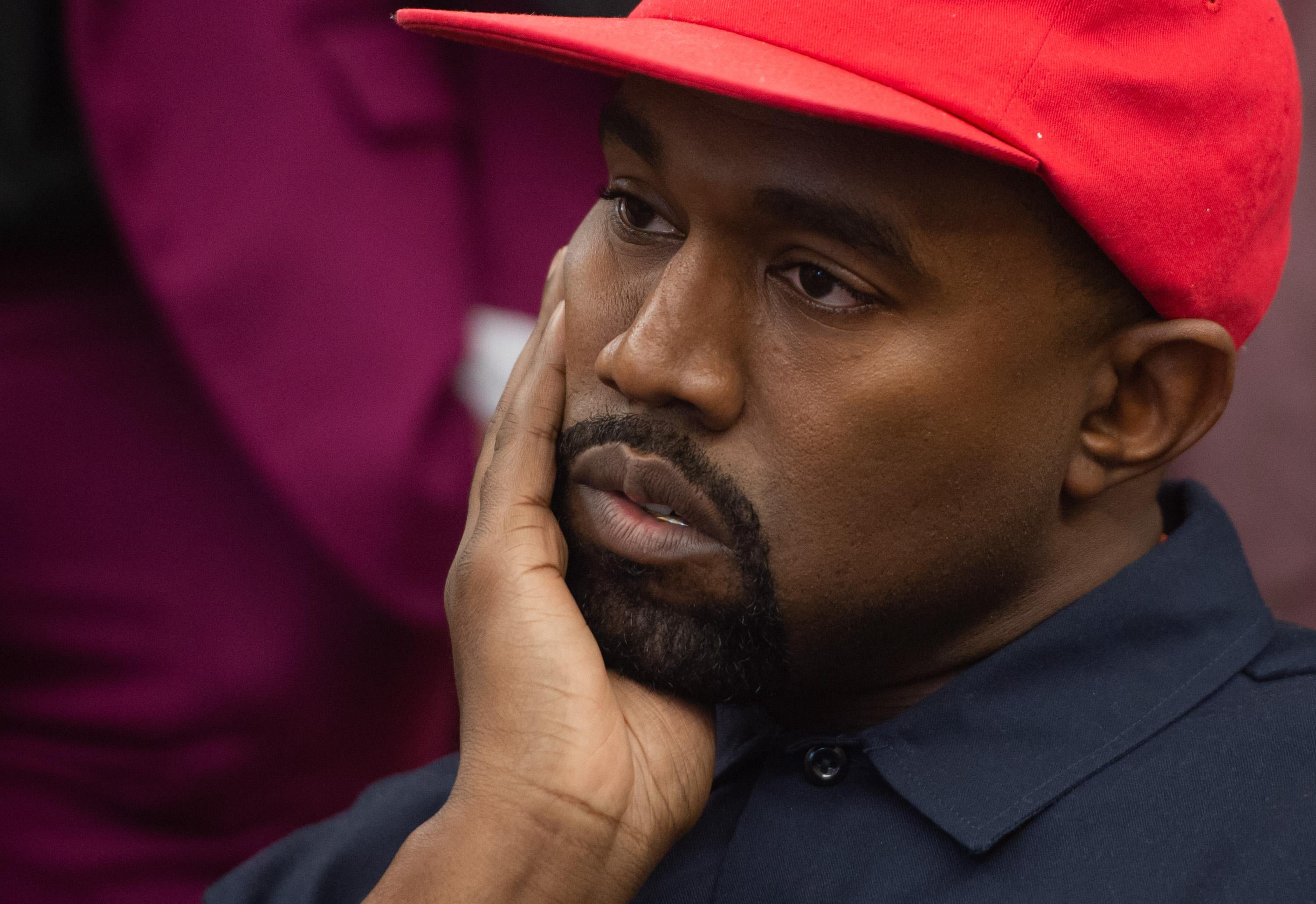 Kanye West wears a red hat and holds his hand to his cheek.