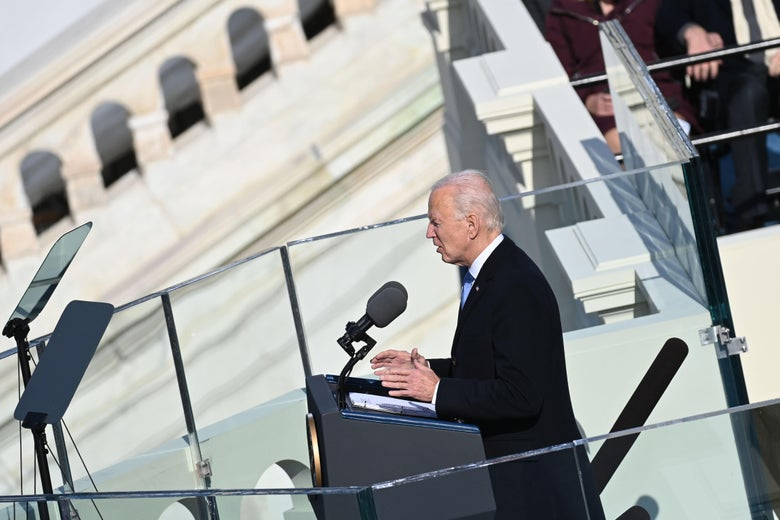 Biden speaking at the lectern seen from the side.