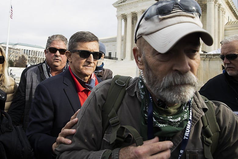 Michael Flynn standing in a group of protesters. Flynn wears sunglasses and puts his hand on the arm of a man in front of him who is wearing a Trump lanyard.