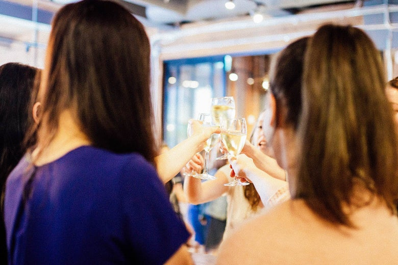 Co-workers standing in a circle clinking wine glasses in the office