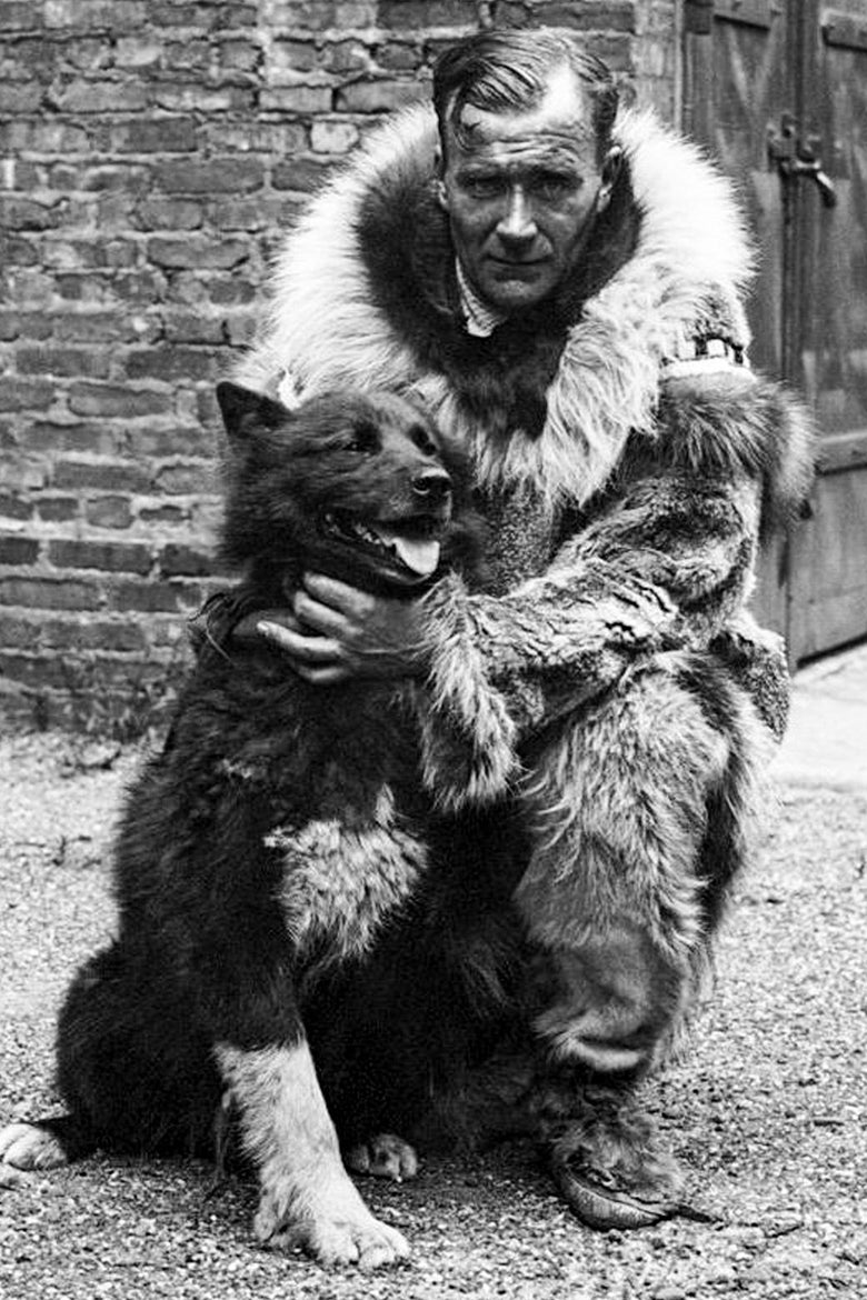 A man in a large fur jacket crouches next to a black and white dog.