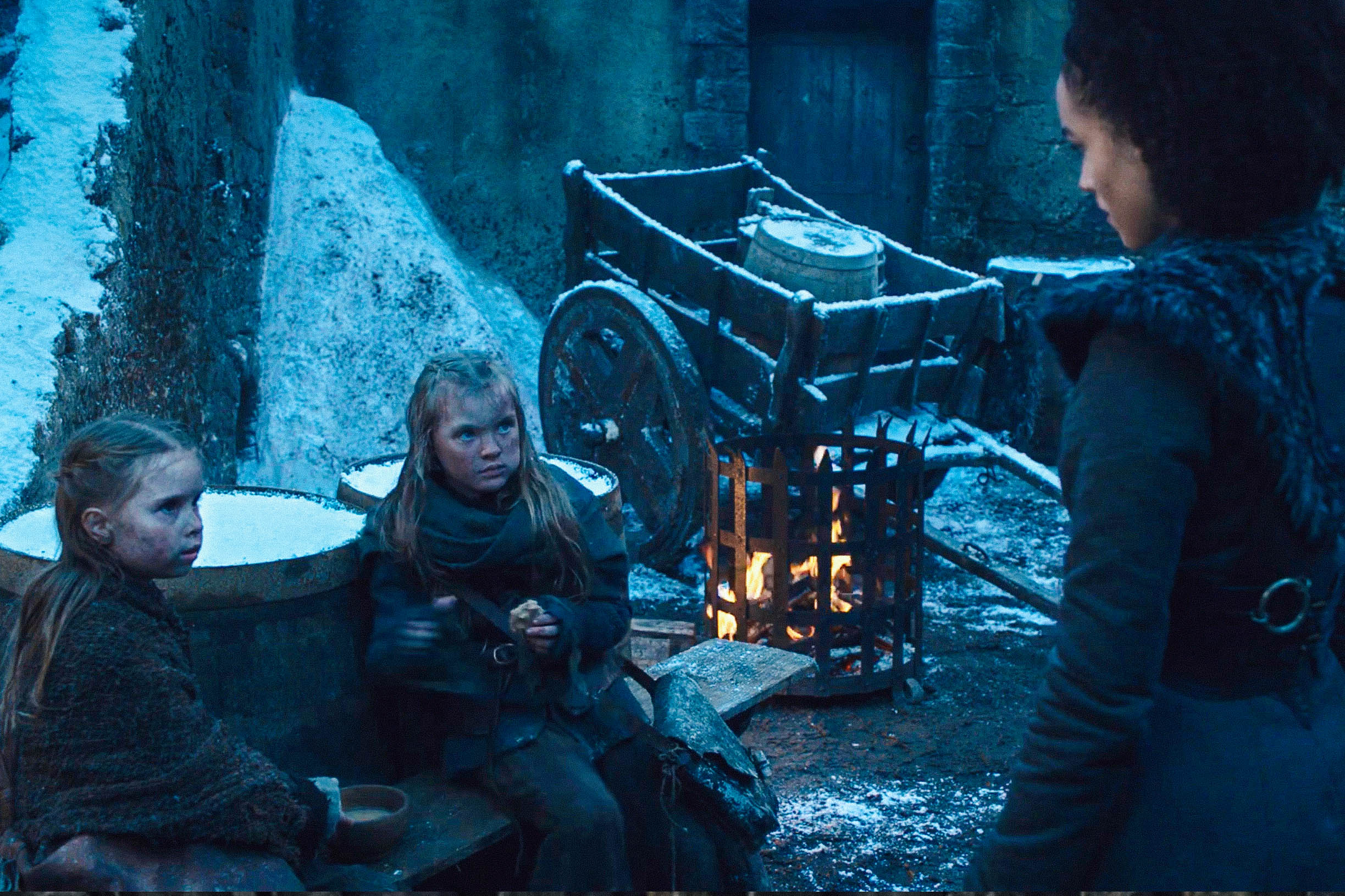 Two young white girls in Winterfell's courtyard look suspiciously at Missandei.