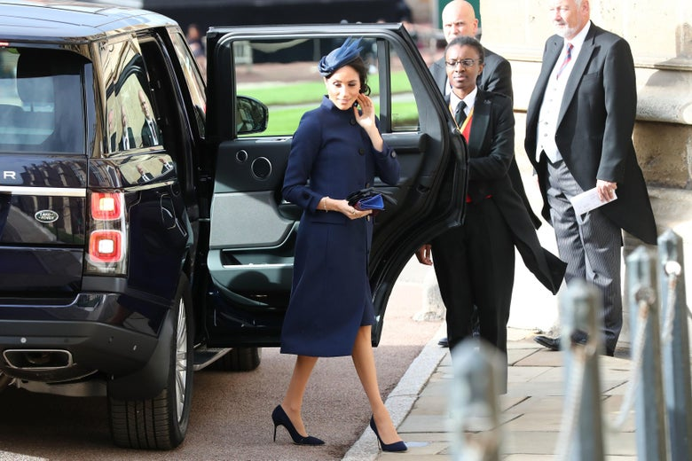Meghan Markle steps out of an SUV in a navy blue coat.