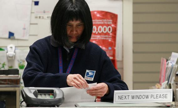 A US Postal Service worker sorts paperwork.