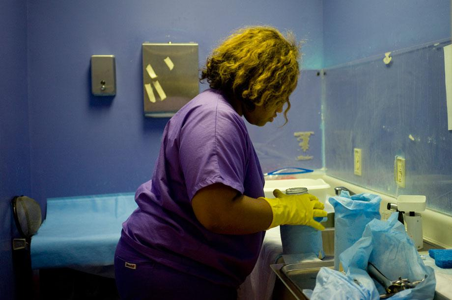 Aarimis Armstrong, 21, a scrub technician, prepares to weigh a specimen after a procedure in November 2012. Armstrong began working at the clinic a week after she had her own abortion there. She said she wanted to use her experience of what it felt like to make the decision. Having an abortion, she said, had been the only option for her.