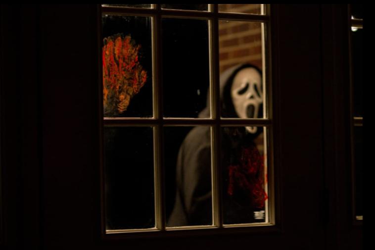 Ghostface behind a bloody window in Scream 4.