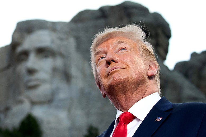 Donald Trump smiles with Mount Rushmore visible behind him.