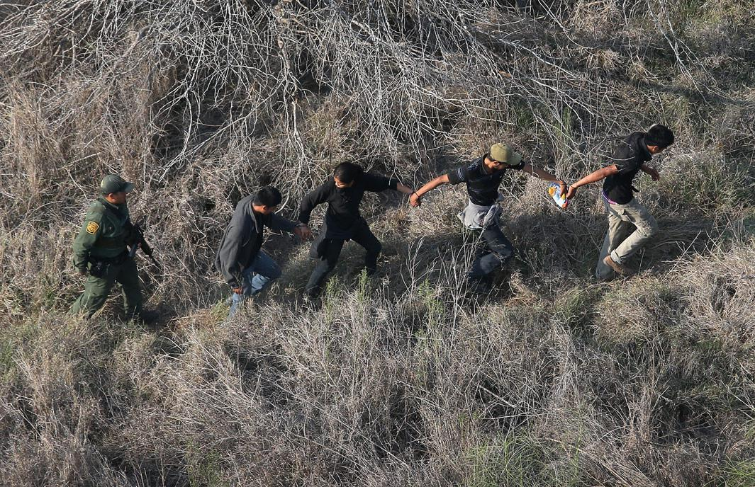 Havana, Texas A U.S. Border Patrol agent escorts a group of undocumented immigrants into custody with helicopter support from the U.S. Office of Air and Marine on May 20, 2013 near the U.S.-Mexico border in Havana, Texas. The Rio Grande Valley area has become the busiest sector for illegal immigration on the whole U.S.-Mexico border with more than a 50 percent increase in the last year.