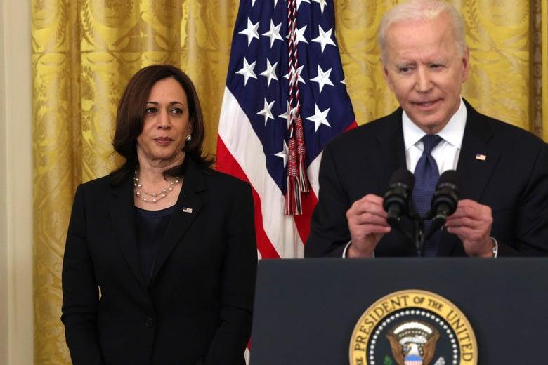 Harris looks at Biden as he speaks at a lectern.
