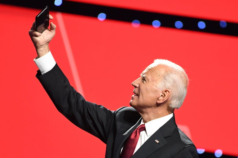 Joe Biden on the debate stage, raising his phone above his head.