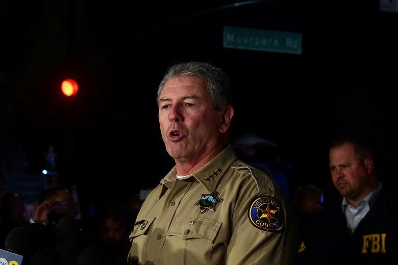 Ventura County Sheriff Geoff Dean speaks. An FBI reporter stands behind him. It is a dark night.