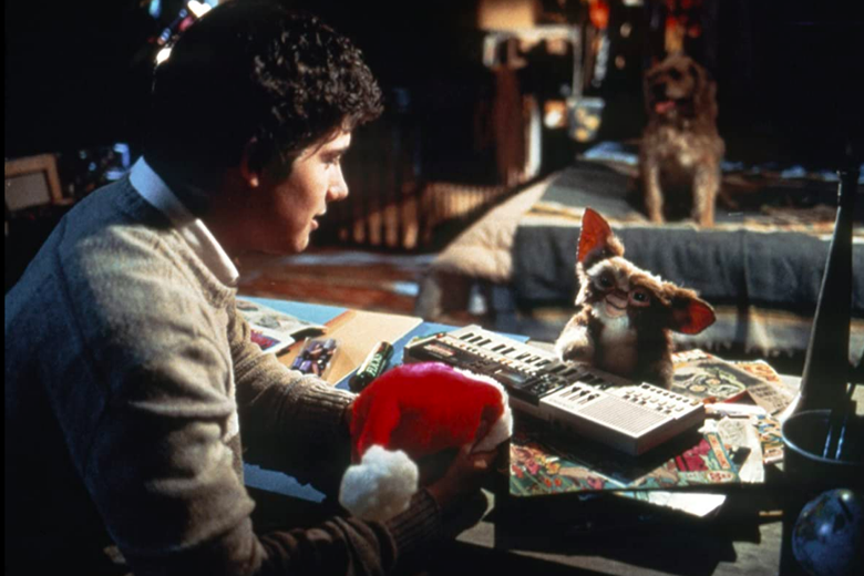 A small creature with big eyes and pointy ears sits at a keyboard in front of Zach Galligan, who holds a Santa hat.