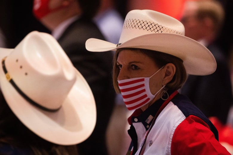 A woman wearing a U.S. flag–branded mask and a cowboy hat