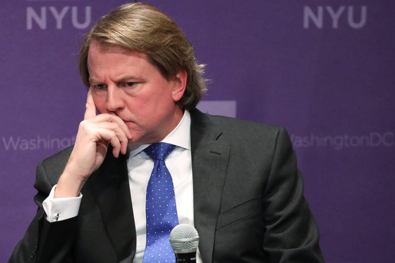 McGahn seated onstage in front of a mic, holding his face and listening.