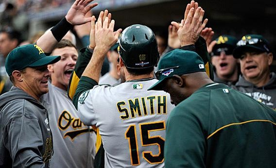 Seth Smith #15 of the Oakland Athletics is congratulated by teammates in the dugout after Smith scored.