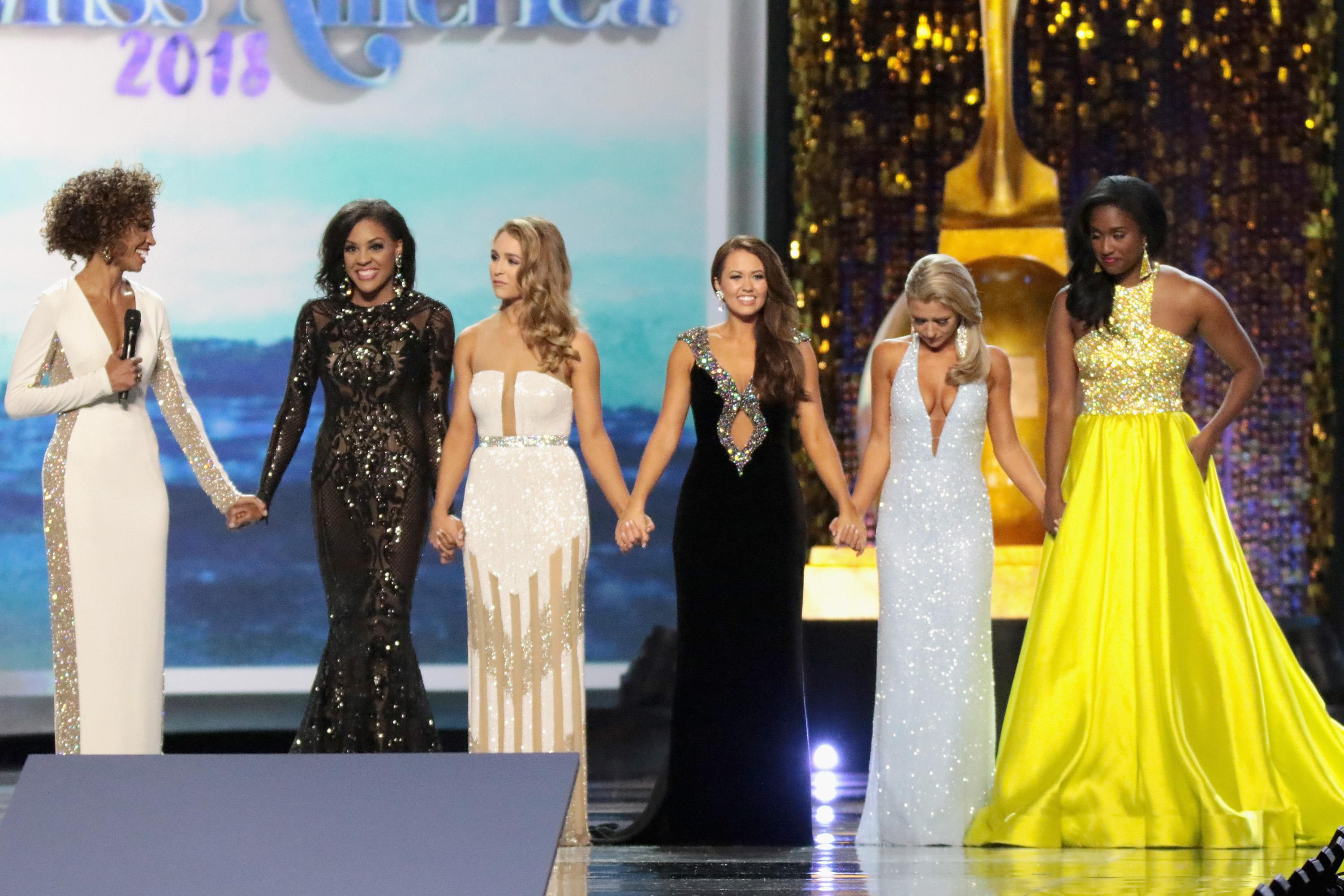 Miss America contestants dressed in gowns hold hands on a stage