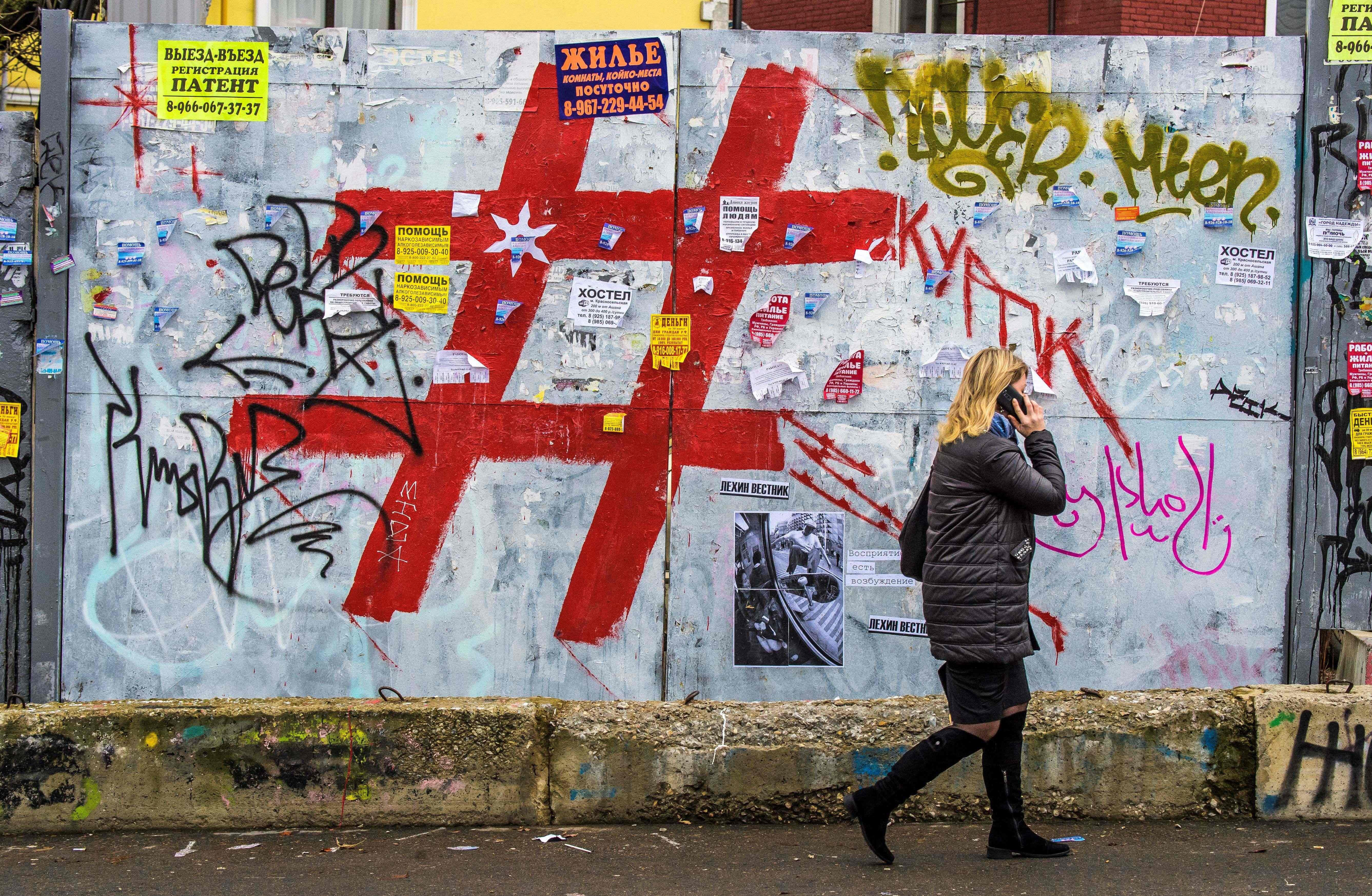 A woman speaks on a mobile phone as she walks past a graffiti covered wall with a giant hashtag sign near Moscow's Kursky railway station on November 17, 2017. / AFP PHOTO / Mladen ANTONOV        (Photo credit should read MLADEN ANTONOV/AFP/Getty Images)