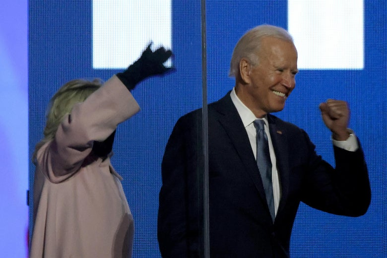 Joe Biden grins and pumps his fist next to his wife, Jill, who waves to the crowd.