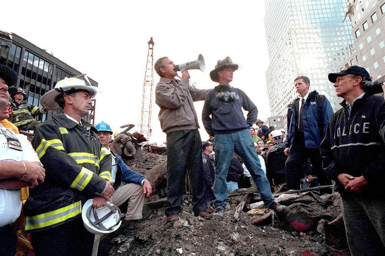 Bush uses a bullhorn as he stands on rubble surrounded by rescue workers, firefighters, and police.