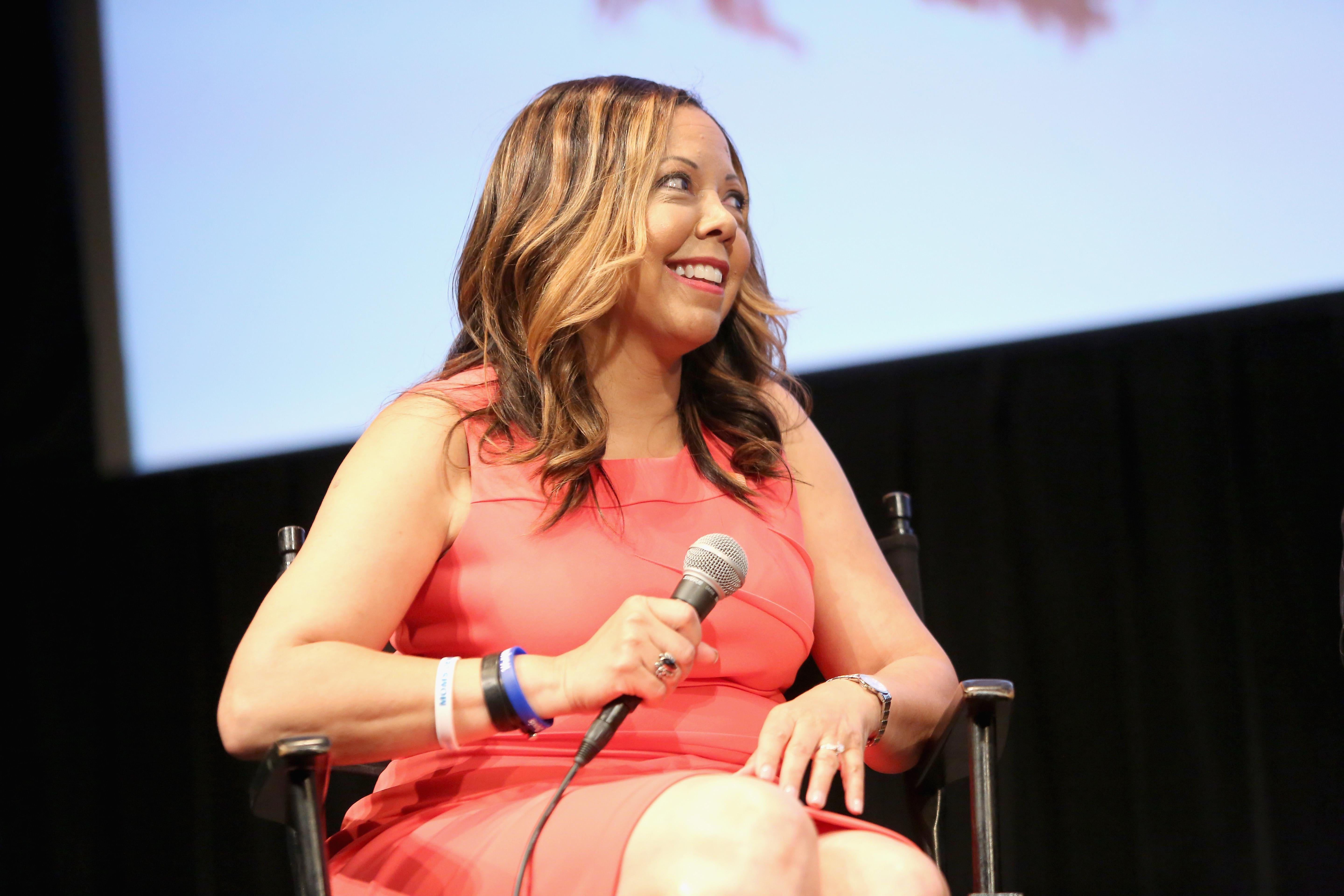 Lucy McBath seated onstage, holding a mic.