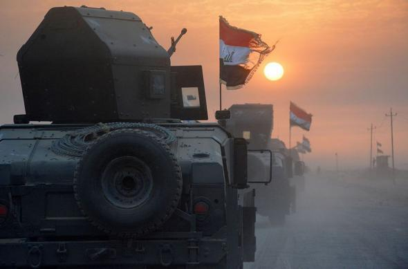 Pro-government forces drive in military vehicles in Iraq's eastern Salaheddin province, south of Hawijah, on October 10, 2016.