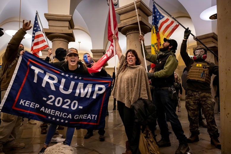woman yelling while holding a trump flag, a woman holding an American flag, and some dudes cosplaying as militia members inside the Capitol