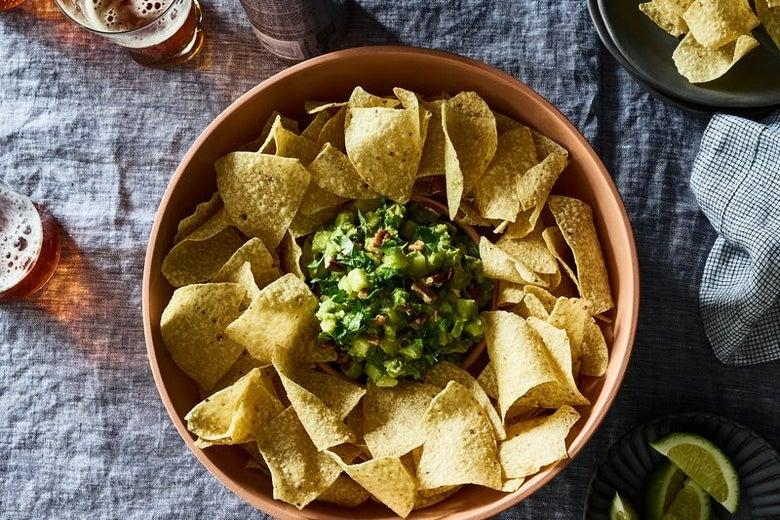 A bowl of tortilla chips, arranged in a circle around a pile of guacamole.