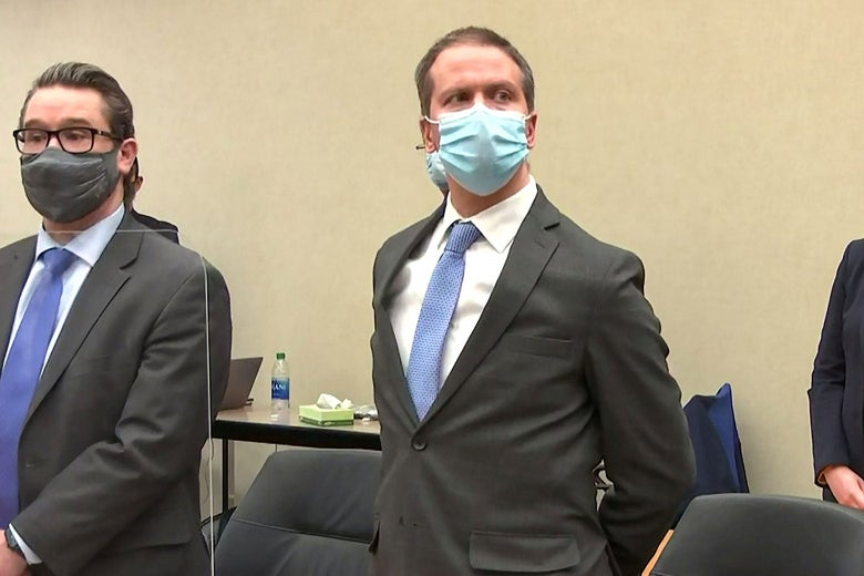 Derek Chauvin stands and looks toward the judge while wearing a mask and a suit with his hands behind his back