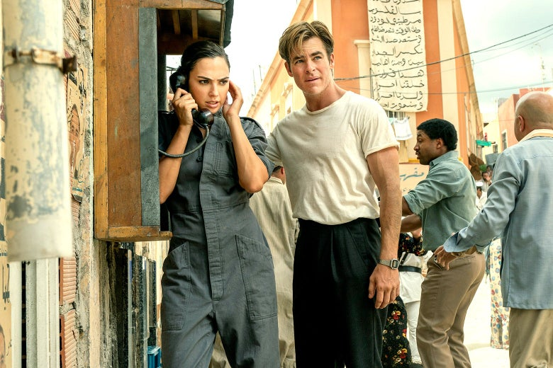 Gal Gadot makes a call on a payphone in a foreign country while Chris Pine stands next to her.